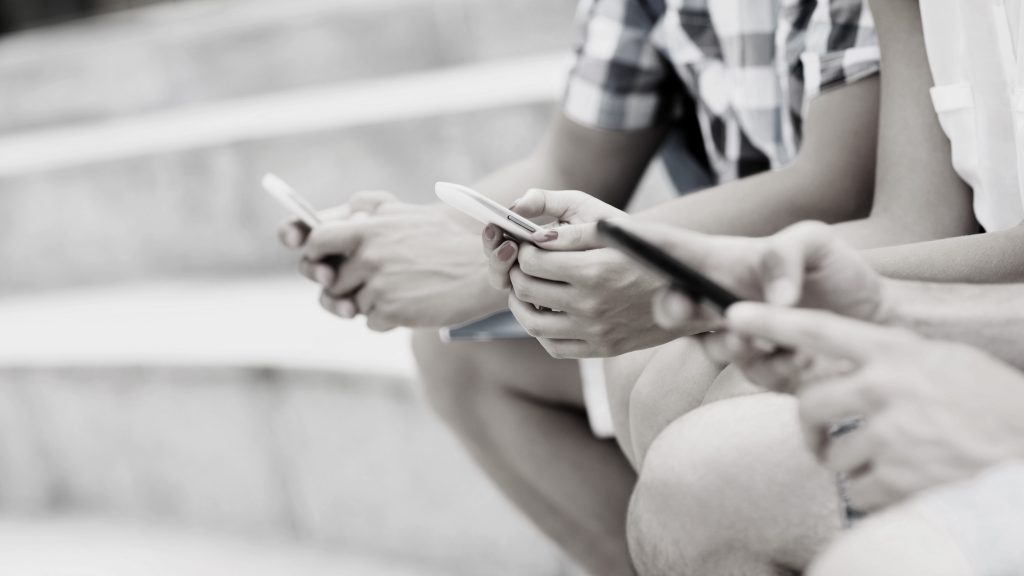 A midsection of students sitting on stairs with their smartphones